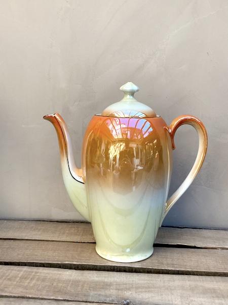 Ensemble constitué d'un théière et d'un pot à sucre en porcelaine d'une jolie couleur porcelaine dégradée orange et nacré, et ornée d'un liseré noir
